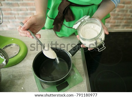 A confectioner in a green apron spoon pours agar-agar into a steel bowl with sugar syrup on the electric stove. cooking marshmallows.Homemade sweet. Homemade marshmallow dessert.  #791180977