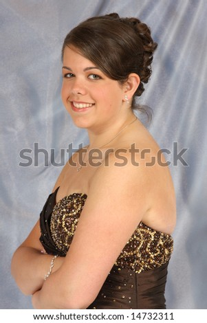 A confident, beautiful young woman dressed up in an evening gown.