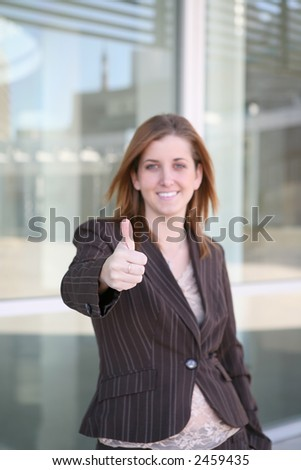 A confident business woman with her thumb up