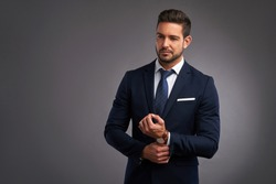 A confident elegant handsome young man standing in front of a grey background in a studio wearing a nice suit