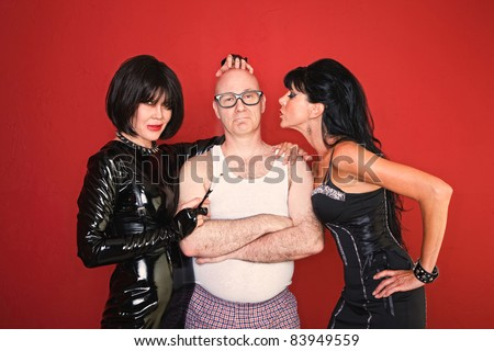 A confident man is surrounded by two playful dominatrix women. - stock photo