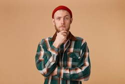 A confident man with a beard dressed in cool red cap and a checkered shirt holds his hand on chin, one eyebrow playfully raised thinks about something, build a plan, ponders a cool idea.