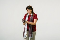 A confident middled-aged Chinese Asian woman is smiling as she texts on her smartphone in a studio against a white background. She is wearing a red blouse, khakis and a beautiful scarf.