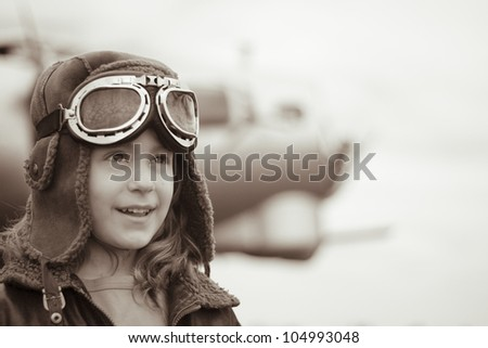 A confident young female pilot is gazing into the distance, wearing flight jacket / hat / goggles.  Bomber is visible in the background out of focus.