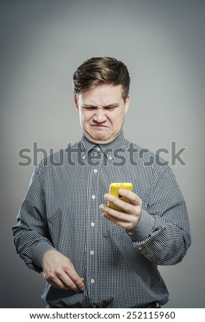 A confused young man looking at mobile phone