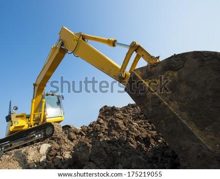 A construction backhoe on a dirt hill