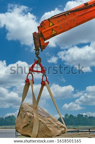 A construction crane lifting a heavy rock in place