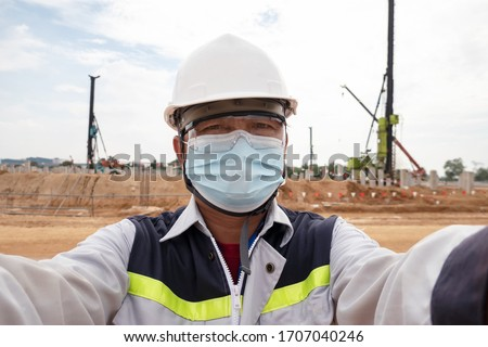 A construction engineer wearing PPE and face mask protect corona virus or Covid19 working at construction site