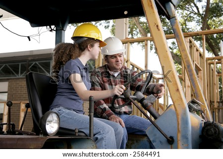 A construction foreman instructing a new worker on driving heavy equipment. Focus on the foreman.