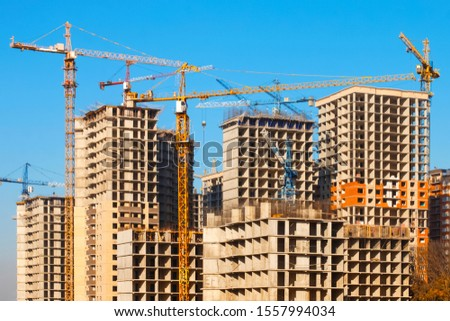 A construction site with a large number of tower cranes working in dense urban areas. The concept of overpopulation of the planet and big cities. Multistorey residential building. City landscape.