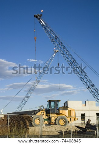 A construction site with cranes and earth mover