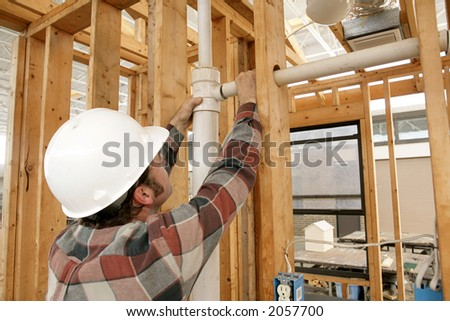 A construction worker connecting plumbing pipe in an unfinished wall. Focus is on the connecting pipes.