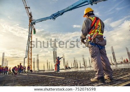 Photo of  A construction worker control a pouring concrete pump on construction site and sunset background