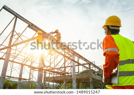 A construction worker control in the construction of roof structures on construction site and sunset background