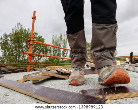 A construction worker has an accident while walks through a site with debris and stepping on a nail  #1398989123