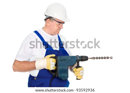 A construction worker holding drill for concrete and wearing proper safety equipment according to OSHA regulations, isolated on white background