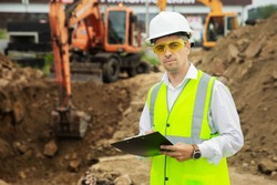 a construction worker in a white helmet with a tablet against the background of an excavator digging a hole