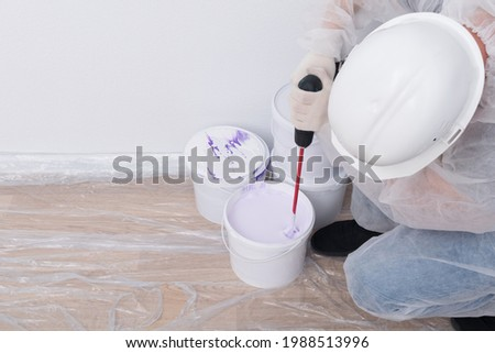 a construction worker in protective clothing and a helmet mixes paint with a mixer in a bucket, against the background of a white wall, there is a place for the inscription Foto stock ©