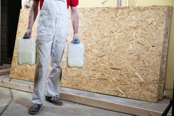 A construction worker in working clothes, holding two plastic canisters. Renovation of house, flat with a professional construction team.