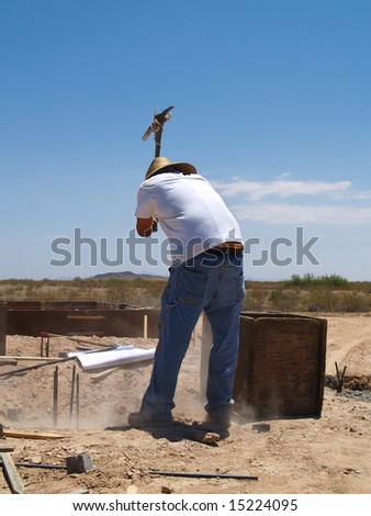 A construction worker is working on an excavation site.  He is about to swing a pickax into the ground.  Vertically framed shot.