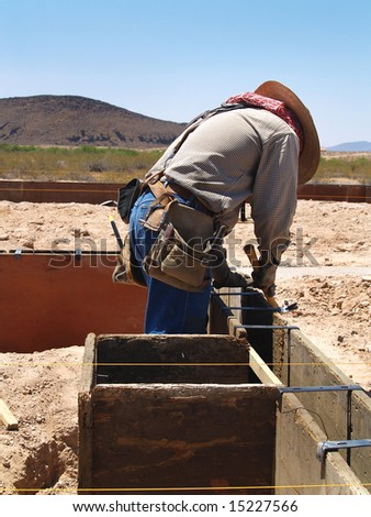 A construction worker is working on an excavation site.  He is looking down at his hammer.  Vertically framed shot.
