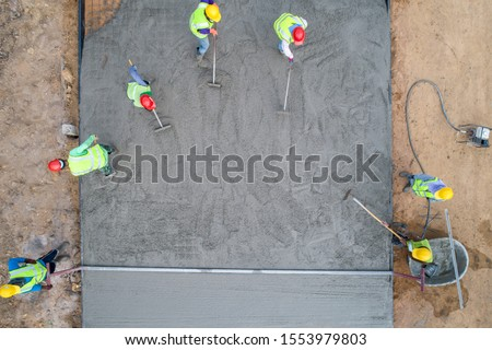 A construction worker pouring a wet concret at road construction site ストックフォト ©