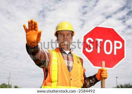 A construction worker stopping traffic, holding a stop sign.