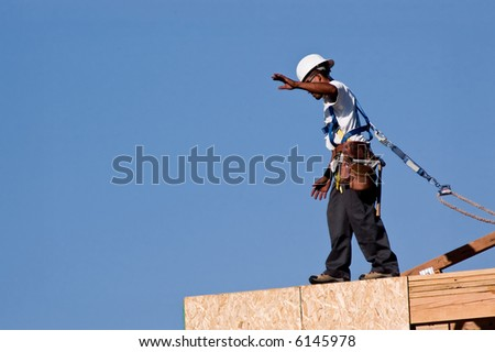 A construction worker walking across the top edge of a second story wall.