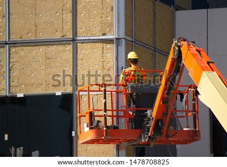 A construction worker, working at heights is harnessed to his sky lift and wearing safety gear. He is using a high speed grinder with a cutting wheel to cut an access panel in a metal plate.