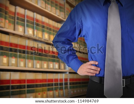 A consultant man is standing in front of a law library of books with copy space area. Use it for a attorney or education concept.