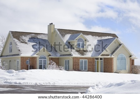 A contemporary new brick home with lots of snow.