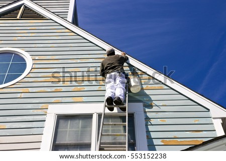 A contractor or painter on a ladder doing exterior paint work, trim work and repairs on a house with wood siding.