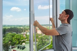A contractor worker installing mosquito wire screen on house plastic windows to protect from insects.