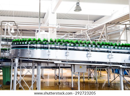 A conveyer belt with empty bottles for beer is seen during production process in a brewery.