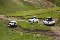 a convoy of cars is moving along a dirt road. travel by car in the mountains. rough road in the steppe. jeeps make their way through the desert