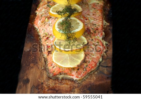 A cooked fillet of sockeye salmon with dill and lemon on cedar plank