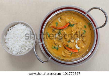 A cooking pan full of chicken and mushroom curry with a cashew nut sauce, garnished with cashews, coriander and chillies with a bowl of rice from above.