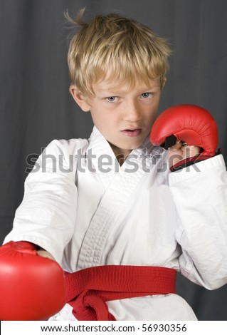 a cool and focused little blonde boy with his pads and karate suit