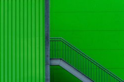 A cool background shot of a green wall with metal stairs
