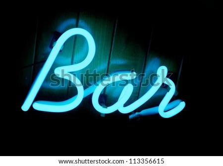A cool blue lit neon bar sign on a teak wood paneled wall