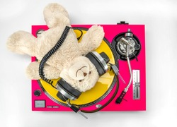 a cool DJ teddy bear lying and relaxing on top of pink turntable with yellow vinyl