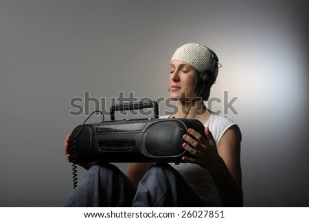 a cool looking girl listening music with stereo and headphones