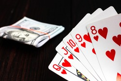 A cool poker hand is a royal flush and a wad of money on a dark wooden table.