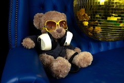 a cool teddy bear with headphones and sunglasses on a sofa with a golden discoball spinning