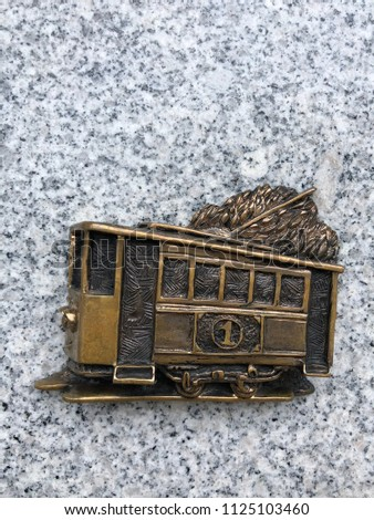 a copper bas-relief depicting an old tram. Vintage tram on the stone background #1125103460