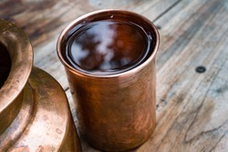 A copper water holder and a glass. In Indian ayurvedic culture it has been established that drinking water out of a copper utensil has many health benefits.