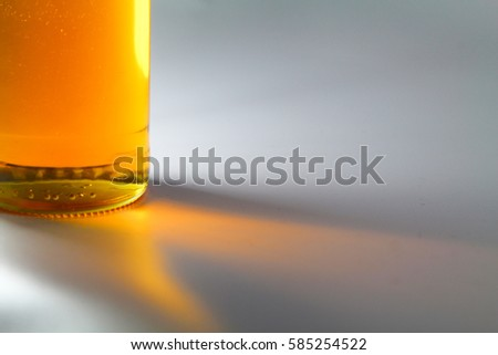 Stock Photo A copy space concept of an apple juice, honey, yellow liquid in a glass bottle illuminated by light with a gradient yellow orange color shadow reflection. Isolated on white background