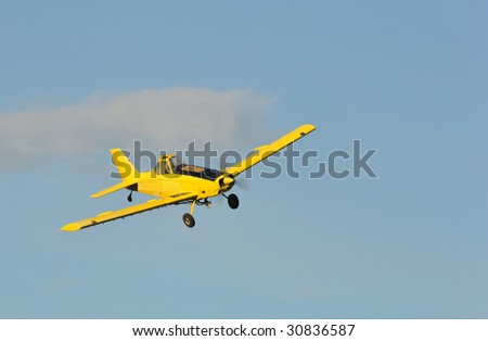 A corp duster or agricultural aircraft flying in a blue sky