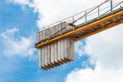 A counterweight of concrete blocks on the tail of a tower crane against a blue sky with clouds. Close-up