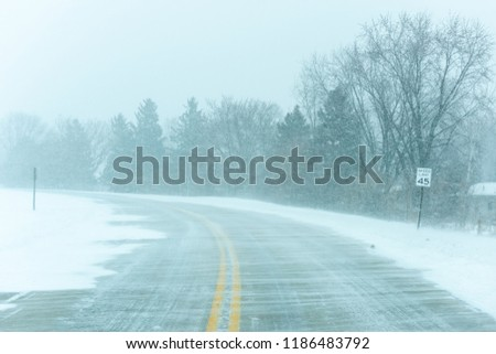 A country highway with snow drifts and while a blizzard is happening.